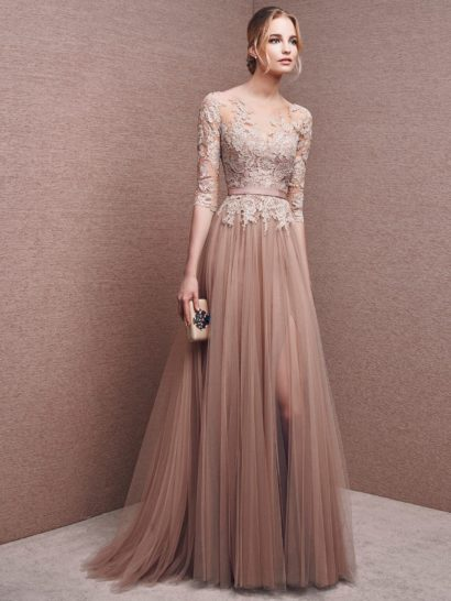 Элегантное вечернее платье темного кремового цвета обрисовывает силуэт прямым кроем, выразительно воплощенным в шифоне, множеством вертикальных складок ниспадающим от линии талии.  Выделить ее помогает узкий атласный пояс. Верх платья покрыт полупрозрачной вставкой, скрывающей декольте и образующей длинные облегающие рукава.  По всей длине она декорирована кружевными аппликациями нежного бежевого оттенка.