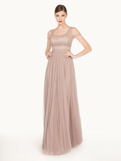 Изысканный образ создает необычное вечернее платье с силуэтом в ампирном стиле. Завышенная линия талии очерчена широким поясом с вышивкой из крупных серебристых бусин. Многослойная юбка из фатина украшена лишь драпировками, спускающимися вертикально. Верх с глубоким округлым вырезом дополнен полупрозрачными рукавами прямого кроя, расшитыми бисером, как и сам лиф.