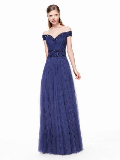 Вечернее платье в пол глубокого синего цвета стильно обнажает плечи портретным декольте, которое оформлено по краю широкой полосой фактурной сияющей вышивки.  Такой же декор покрывает и широкий пояс на линии талии.  Лиф сердечком декорирован множеством драпировок и складок, спускающихся по диагонали, а многослойную юбку прямого силуэта тоже украшают складки – они идут вертикально от талии по подолу.
