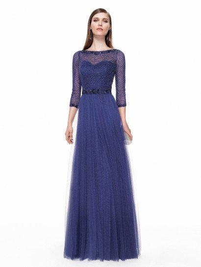 Закрытое свадебное платье незабываемого синего цвета сочетает классическую элегантность с современными деталями вроде полупрозрачного верха.  Вставка скрывает лиф в форме сердечка, образуя женственный вырез лодочкой и прямые рукава длиной в три четверти.  Манжеты, вырез и линию талии украшает плотный слой вышивки из сверкающих бисерин темного синего цвета.  Юбка из фатина спускается прямым кроем по фигуре.