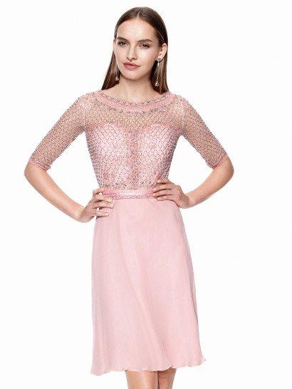 Короткое вечернее платье пудрового розового оттенка красиво акцентирует фигуру изящным прямым кроем. Сдержанный верх создает полупрозрачная вставка, скрывающая декольте в форме сердца и образующая округлый вырез и рукава длиной до локтя. От самой талии вставка расшита геометрическим узором из сверкающего серебристого бисера, а края выреза и манжеты дополнительно декорированы широкой розовой тесьмой. Платье идеальноподойдет для встречи Нового года!