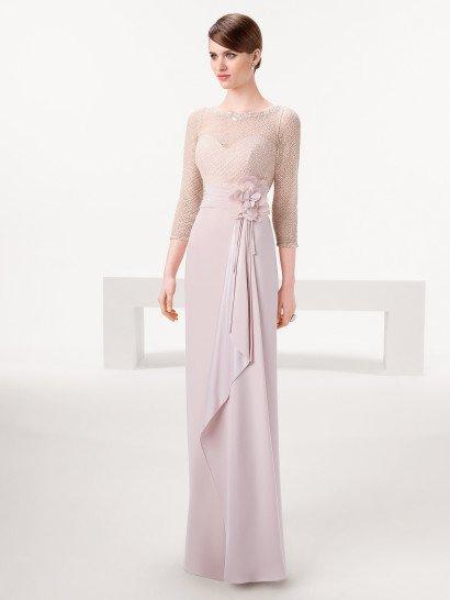 Прямое вечернее платье нежного розового цвета создает романтичное настроение деталями.  Талию выделяет широкий пояс, украшенный сбоку пышным цветком с плотными лепестками, а от него вниз на подол спускаются длинные ленты.  Лиф дополняет полупрозрачная вставка, расшитая бисером, образующим геометрический узор.  Он покрывает и область декольте, и рукава длиной в три четверти, выполненные из той же прозрачной ткани.  Наденьте это платье на встречуНовогоГода!