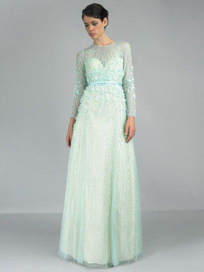 Закрытое вечернее платье нежного мятного оттенка зеленого красиво подчеркивает фигуру прямым силуэтом с элегантно акцентированной талией – ее выделяет узкий атласный пояс, подобранный в тон ткани.  По всей длине платье покрывает полупрозрачная ткань, создающая закрытый вырез под горло и длинные рукава прямого кроя.  Она декорирована вышивкой из бисера с мягким блеском, располагающейся вертикальными полосами, и крупными лепестками из плотной ткани у талии.  Наденьте это платье на встречуНового Года 2016!