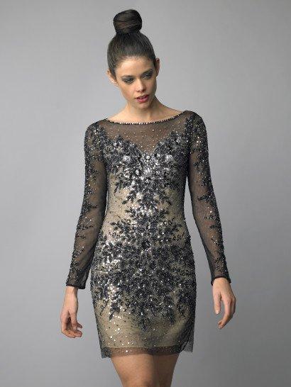 Прямое вечернее платье длиной до середины бедра красиво сочетает пудровый бежевый тон подкладки и выразительный черный цвет верхнего слоя ткани.  Полупрозрачный верх закрывает вырез в форме сердечка, образует вырез лодочка и длинные облегающие рукава.  Вечернее платье декорировано сияющей вышивкой из крупных бусин, бисера и серебристых пайеток.  Растительный узор становится наиболее плотным на лифе и на уровне бедер, подчеркивая изгибы фигуры.  Наденьте это платье на встречуНовогоГода 2018!