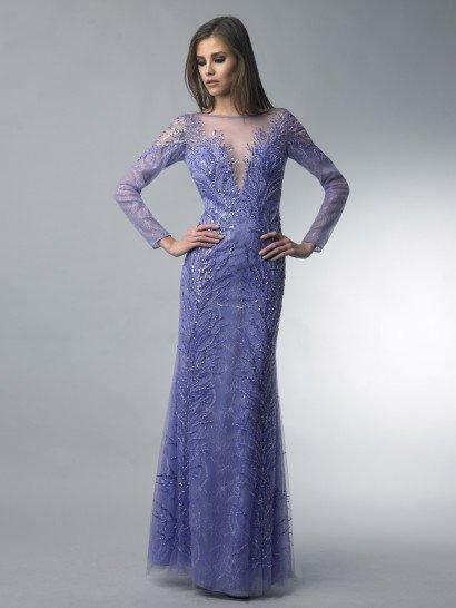 Необычный фиолетовый оттенок вечернего платья прекрасно сочетается с оригинальным кроем.  Глубокое соблазнительное декольте закрыто полупрозрачной вставкой, которая скрывает и плечи, и образует рукава прямого кроя.  Края декольте выразительно украшены сияющей вышивкой из пайеток разных оттенков фиолетового.  Декор спускается вертикальными полосами и на подол прямого кроя, доходя до самого пола.  Платье идеальноподойдет для встречи Нового года!