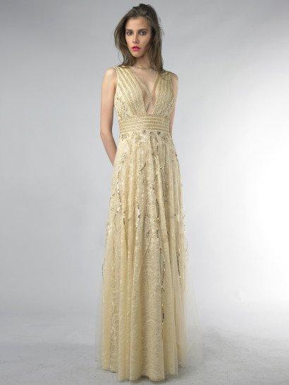 Изысканный силуэт прямого кроя создает золотое вечернее платье с широким поясом, образованным несколькими горизонтальными полосами отделки.  Такие же полосы тесьмы декорируют и смелое V-образное декольте.  По бокам лифа и верхнему слою ажурной ткани на юбке располагается причудливая вышивка из серебристых пайеток и золотистых бусин, образующая нежный растительный узор.  Он прекрасно дополняет кружевную текстуру ткани и уравновешивает соблазнительность лифа романтичностью.