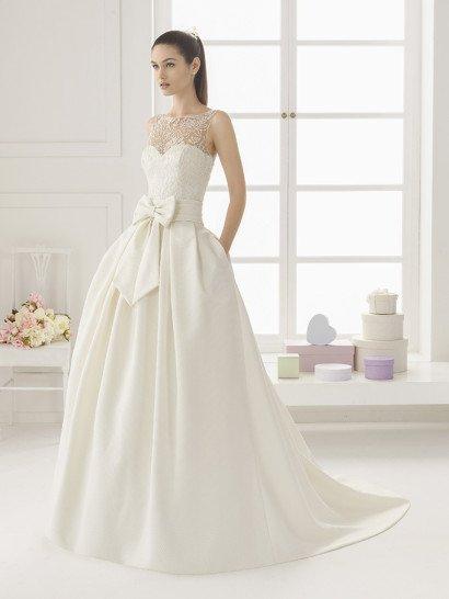 Пышное свадебное платье с великолепной юбкой из фактурного шелка-микадо.  Юбка свадебного платья с кокетливым широким поясом с объемным бантом спереди, ленты от него спереди спускаются на подол.  Открытый корсет с традиционного кроя лифом полностью покрыт глянцевой кружевной тканью, которая скрывает область декольте.  Торжественность образу придает пышный шлейф, завершающий объемную юбку полукругом.