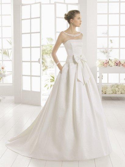 Пышное свадебное платье струится по фигуре элегантными объемными складками атласной ткани, переходящими в полукруг аристократичного шлейфа.  Открытый лиф с лаконичным прямым декольте изысканно дополняет прозрачная вставка, декорированная кружевными аппликациями вокруг округлого выреза у шеи и на манжетах, расположенных на запястьях.  Скрытые карманы и широкий пояс с крупным бантом делают образ особенно запоминающимся.  Свадебное платье 2016 года