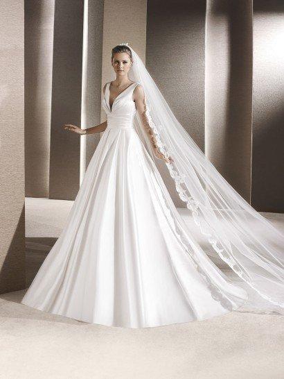 Пышный силуэт свадебного платья становится изящным и аристократичным благодаря мягкому сиянию атласной ткани.  Впечатляет красотой атласная юбка – фактурные складки, идущие от линии талии, спускаются по всей длине подола, а сзади ее завершает прекрасный шлейф.  Элегантны и линии лифа – глубокое V-образное декольте, очерченное широкими бретелями, изысканно подчеркивает фигуру. Талия стильно обрисована широким поясом с горизонтальными складками ткани.  Свадебное платье 2016 года