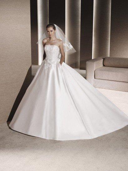 Незабываемо красивое свадебное платье с пышным силуэтом выполнено из роскошного глянцевого атласа.  Лаконичная юбка с многослойной подкладкой дополнена лишь широким полукругом шлейфа, который подчеркивает элегантную торжественность образа.  Открытый лиф прямого кроя оформлен плотным слоем кружевных аппликаций.  Спускается кружево и на корсет, а также продолжается изящными вертикальными полосами чуть ниже линии талии.