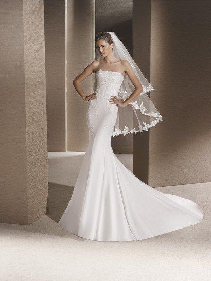 Лаконичное свадебное платье с силуэтом «русалка» создаст женственный, невероятно романтичный образ.  Верх платья с открытым лифом прямого кроя декорирует слой тонкого кружева с мелким рисунком, кружевная ткань спускается и на верхнюю часть подола.  Изысканная юбка из шелка спускается вертикальными складками и потрясающе завершает образ длинным шлейфом, простирающимся позади роскошным полукругом.