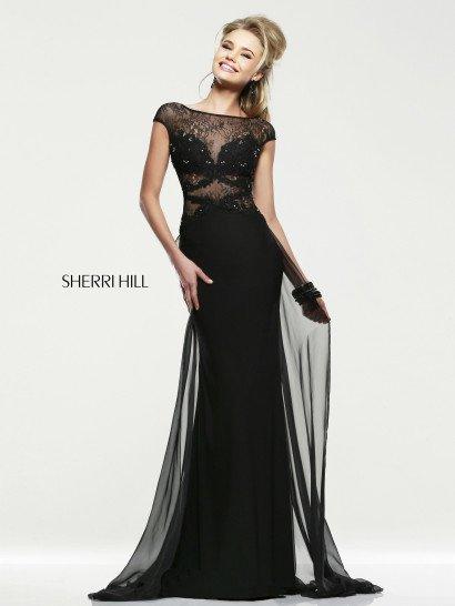 Роскошное коктейльноеплатье прямого кроя выполнено в стильном и загадочном черном.  Соблазнительный лиф дополнен полупрозрачными ажурными вставками и полосами фигурной тесьмы, а также вышивкой из серебристых пайеток.  Элегантная облегающая юбка, спускающаяся до самого пола, дополнена слоем полупрозрачного шифона, который образует своего рода шлейф, подчеркивающий силуэт при каждом движении.