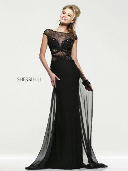 Роскошное вечернее платье прямого кроя выполнено в стильном и загадочном черном. Соблазнительный лиф дополнен полупрозрачными ажурными вставками и полосами фигурной тесьмы, а также вышивкой из серебристых пайеток. Элегантная облегающая юбка, спускающаяся до самого пола, дополнена слоем полупрозрачного шифона, который образует своего рода шлейф, подчеркивающий силуэт при каждом движении.