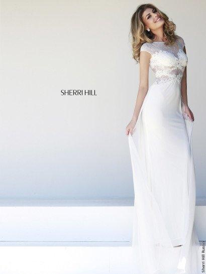 Стильное вечернее платье белого цвета безупречно обрисовывает каждый изгиб фигуры.  Чувственное оформление верха впечатляет – лиф декорирован плотным кружевом, а ниже и выше него располагаются полупрозрачные ажурные вставки, дополненные полосами фигурной тесьмы.  Вставка образует небольшие рукава и округлый вырез, подчеркивающий шею.  Юбку украшает легкий струящийся шлейф из шифона.