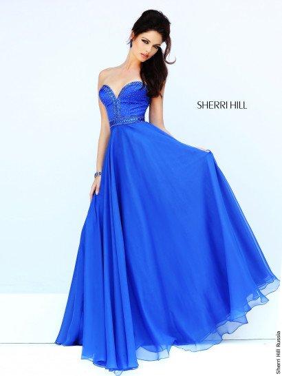 Открытое вечернее платье насыщенного синего оттенка чувственно подчеркивает фигуру глубоким декольте в форме сердечка, декорированным вышивкой из бусин в тон ткани.  Такой декор покрывает и весь лиф до естественной линии талии, которая очерчена небольшим поясом с горизонтальными полосами вышивки.  Многослойная юбка выполнена из легкого полупрозрачного шифона.