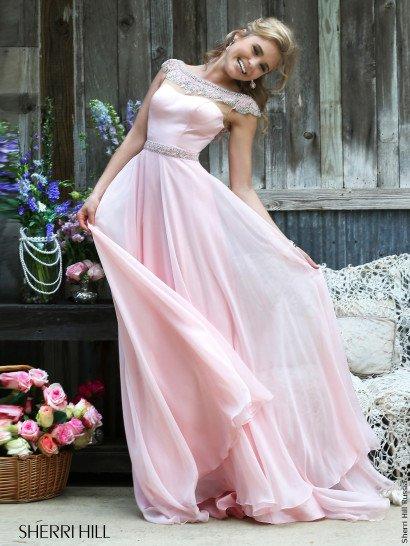 Нежный вечерний образ создает прямое розовое платье из глянцевого атласа и воздушного шифона, в несколько слоев покрывающего длинную юбку.  Элегантные линии декольте подчеркнуты необычным воротником с вырезом лодочка, скрывающим плечи – он полностью расшит фактурной вышивкой из крупных бусин и бисера.  Выделить в силуэте талию помогает узкий пояс с отделкой, повторяющей декор воротника.
