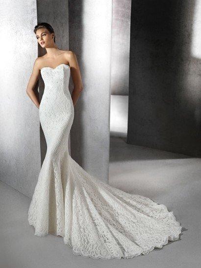 Изысканное свадебное платье с силуэтом «русалка» по всей длине декорировано плотным кружевом, которое делает образ невероятно романтичным.  Кружевная ткань подчеркивает пышность юбки и элегантность небольшого шлейфа.  Дополнить образ можно блузой из легкой полупрозрачной ткани, с широкими длинными рукавами и необычным длинным вырезом «замочная скважина» спереди, сверху застегнутым изящной пуговкой.