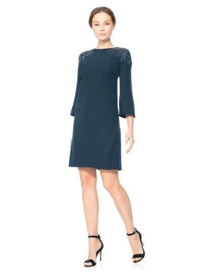 Элегантное вечернее платье прямого силуэта выполнено в невероятно лаконичном стиле из плотной матовой ткани насыщенного синего оттенка.  Плечи, скрытые длинными прямыми рукавами, украшены потрясающей вышивкой из бисера, обрисовывающей края округлого выреза под горло и спускающейся с плеч на рукава.  Юбка длиной до середины бедра позволяет продемонстрировать ноги.