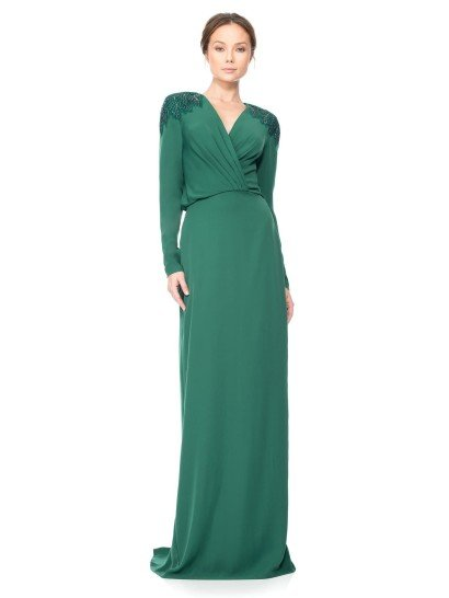 Лаконичное и изысканное вечернее платье насыщенного зеленого цвета стильно обрисовывает фигуру, подчеркивая ее широкими фактурными складками ткани, спускающимися к естественной линии талии по лифа с V-образным вырезом и длинными рукавами прямого кроя.  Плечи вечернего платье украшают выразительные акценты в виде вышивки, выполненной из глянцевого бисера в тон зеленой ткани вечернего платья.
