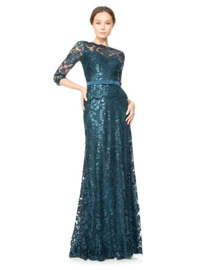 Прямое вечернее платье с подкладкой изысканного изумрудного оттенка покрыто прозрачной тканью, на которой располагаются глянцевые кружевные аппликации в тон.  Прозрачная ткань создает вставку в области декольте, образующую вырез «бато», а также образует рукава длиной в три четверти.  Акцентом в силуэте становится узкий пояс из плотной матовой ткани зеленого цвета, от которого спускается небольшая кружевная баска.  Есть платья больших размеров.