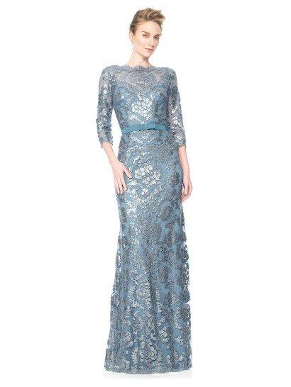 Прямое вечернее платье стильно декорировано глянцевым кружевом серебристого цвета, располагающимся на светлой голубой подкладке.  Полупрозрачная основа для кружева выполнена в таком же нежном голубом цвете.  Над лифом в форме сердечка тонкая ткань располагается вставкой, скрывающей декольте, создающей вырез лодочкой и элегантные рукава длиной в три четверти.  Дополнением к образу служит пояс из плотной матовой ткани.  Есть платья больших размеров.