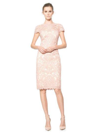 Короткое вечернее платье выполнено в нежном розовом цвете. По всей длине его покрывает слой крупного выразительного кружева с абстрактным узором, расположенного на прозрачной основе.  Кружево создает короткие рукава с фигурными краями и округлый вырез над лифом прямого кроя, а также фестоны по нижней части подола.  В качестве подкладки использована белая хлопковая ткань со стрейчем.  Есть платья больших размеров