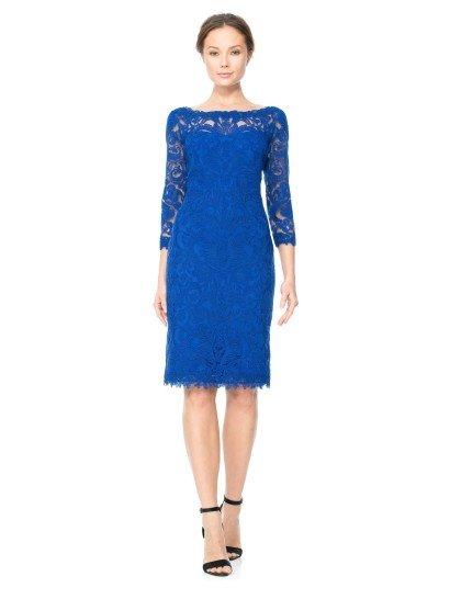 Вечернее платье с силуэтом «футляр» стильно декорировано кружевом, которое расположилось на полупрозрачной ткани.  Она скрывает область декольте, образует вставку с округлым вырезом, красиво подчеркивающим шею, и облегающие рукава длиной в три четверти.  Насыщенный синий цвет, длина до колена и выразительный абстрактный рисунок кружева, образующего фестоны по низу подола, становятся прекрасными украшениями лаконичного образа.