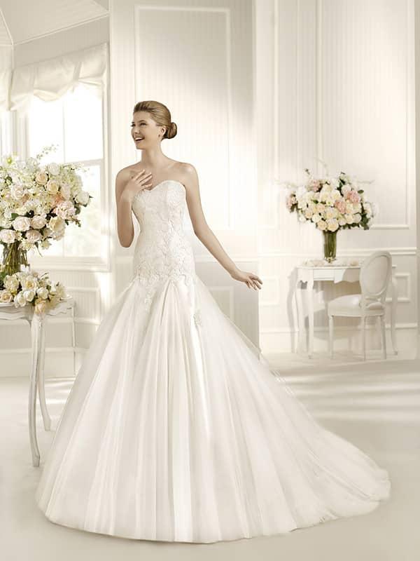 Открытое свадебное платье пышного кроя, декорированное кружевом.