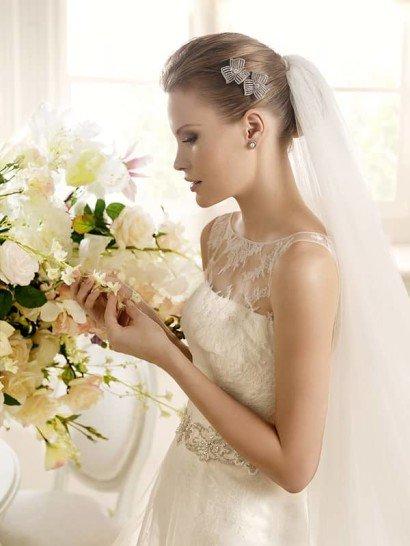 Романтичное свадебное платье с кружевной вставкой над лифом и широким поясом.