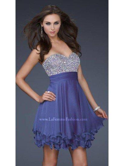 Открытое элегантное коктейльное платье для выпускного сложного серо-фиолетового оттенка.  Лиф – сплошь декорирован стразами.  Обработка срезов многослойной юбки косого кроя создаёт волнистый край.  На талии – широкий драпированный пояс.