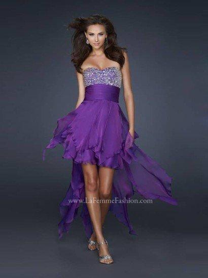 Открытое недорогое платье на выпускной цвета тёмной лаванды.  Лиф с линией декольте в форме «сердечка» сплошь усыпан кристаллами.  Область под грудью обвита широким плиссированным поясом.  Широкая летящая юбка косого кроя с подолом переменной длины оформлена асимметричными срезами.