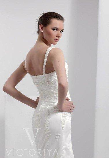Элегантное и недорогое свадебное платье с прямым силуэтом и красивым кружевным шлейфом средней длины.