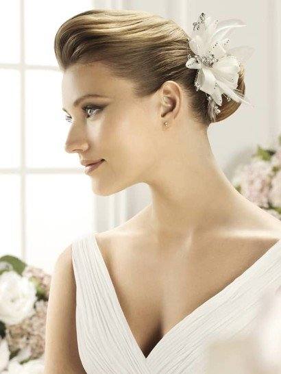 Впечатляющее украшение в прическу создано для самых драматичных невест. Оно представляет собой пышный бутон из белой ткани, дополненный воздушными объемными деталями и серебристой отделкой маленькими стразами и бисером.