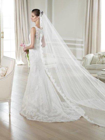 Облегающее свадебное платье с кружевной отделкой и округлым вырезом под горло.