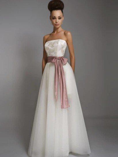 Стильное и недорогое свадебное платье дополнено нежным розовым акцентом. Атласный пояс на стройной талии может стать источником вдохновения для букета невесты или оформления вечеринки.  Прямой сдержанный лиф с открытым декольте без бретелек декорирован вышивкой с мелким изящным рисунком. Объемная юбка с пышным силуэтом выполнена из нескольких слоев матового тюльмарина.