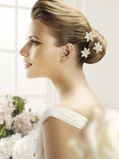 Нежные цветочные бутоны в минималистичном стиле великолепно украшают свадебную прическу. Они выполнены из глянцевой атласной ткани кремового оттенка и украшены маленькими стразами в центре.