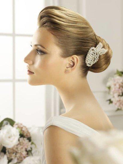 Выразительное украшение для стильной свадебной укладки. Романтичный цветочный бутон из полупрозрачной ткани цвета слоновой кости полностью оформлен элегантными серебристыми стразами среднего размера.