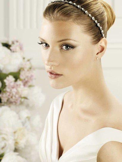 Узкий обруч для свадебной укладки впишется как в эффектный, так и в лаконичный образ невесты. Тонкая серебристая цепочка в роли основы по всей длине дополнена стразами небольшого размера.