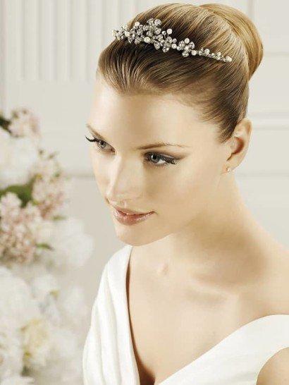 Романтичный обруч способен сыграть роль деликатной свадебной диадемы и безупречно украсить укладку невесты. Он выполнен в серебристых тонах и дополнен небольшими белыми жемчужинами, а также маленькими стразами.