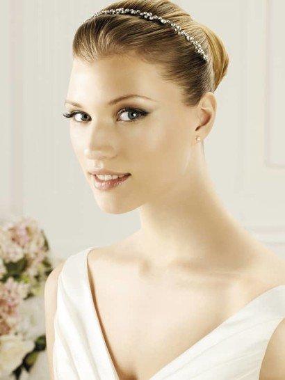 Изящное украшение будет идеальным дополнением сдержанной свадебной укладки. Оно представляет собой узкий обруч, оформленный небольшими каплевидными стразами серебристого цвета по всей длине.