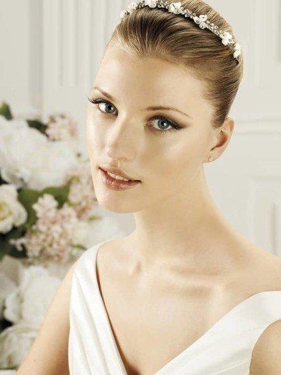 Подчеркните изящество лаконичной свадебной укладки с помощью романтичного обруча, украшенного каплевидными серебристыми стразами и маленькими белыми бутонами.