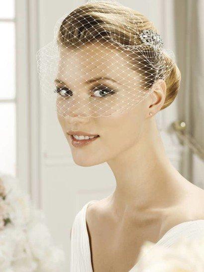 Утонченный свадебный аксессуар – вуаль из крупной сетки, - дополнит образ и придаст ему винтажное настроение. Сбоку вуаль дополнена крупной серебристой брошью, оформленной стразами разных размеров.