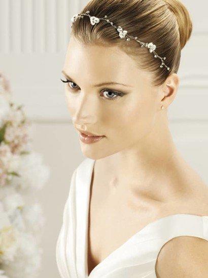 Деликатное украшение для волос, представляющее собой тонкий фигурный обруч. Серебристые веточки, способные элегантно дополнить классическую прическу, украшены небольшими цветочными бутонами с бисерными сердцевинами.