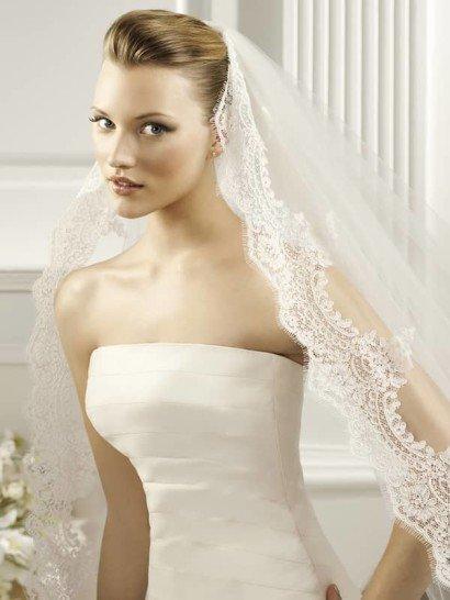 Широкая кружевная кайма с мотивами в стиле рококо, украшенная длинными «ресничками», обрамляет весь периметр величественной свадебной фаты овальной формы из коллекции испанской марки La Sposa Pronovias Fashion Group, образуя волнообразный узор. Красивый резной овал, повторяющий очертания шлейфа платья, придаст свадебному облику невесты королевский шик.  Размер 3x3,5м / 3x4,5м