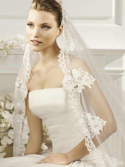 Роскошная кружевная кайма с красивым крупным рисунком в стиле «барокко» украшает периметр этой величественной свадебной фаты овальной формы из коллекции испанской марки La Sposa Pronovias Fashion Group. Волнистый край и длинные «ресничками» кружева красиво обрамляют открытые плечи, создавая поистине сказочный образ невесты.  Размер 3x3,5м / 3x4,5м