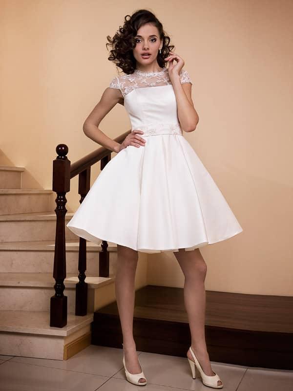 Красивое короткое свадебное платье А-силуэта расшитое пайетками, декорирует область декольте и маленький рукав «крылышко».