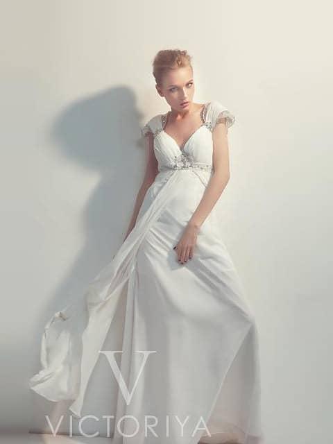 Белое вечернее платье с короткими рукавами и декором из бисерной вышивки.