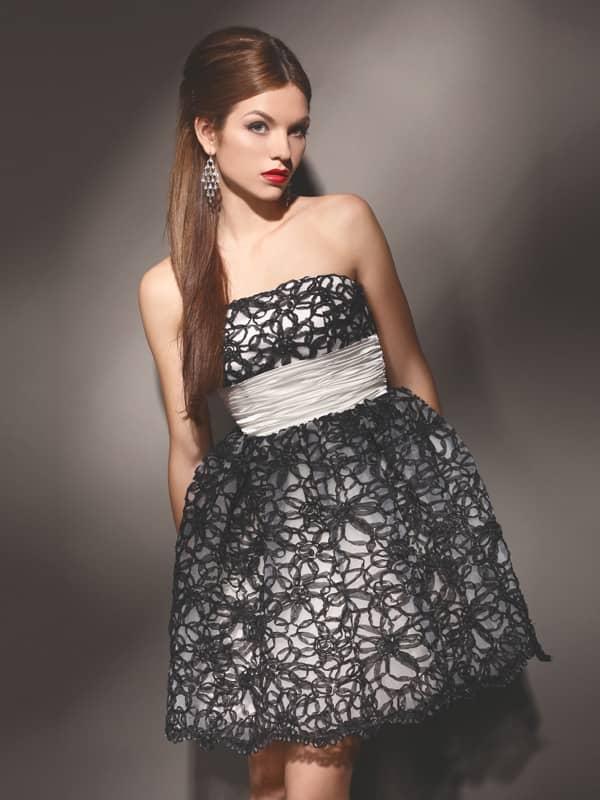 Короткое вечернее платье, декорированное черным кружевом, с широким поясом из белого атласа.