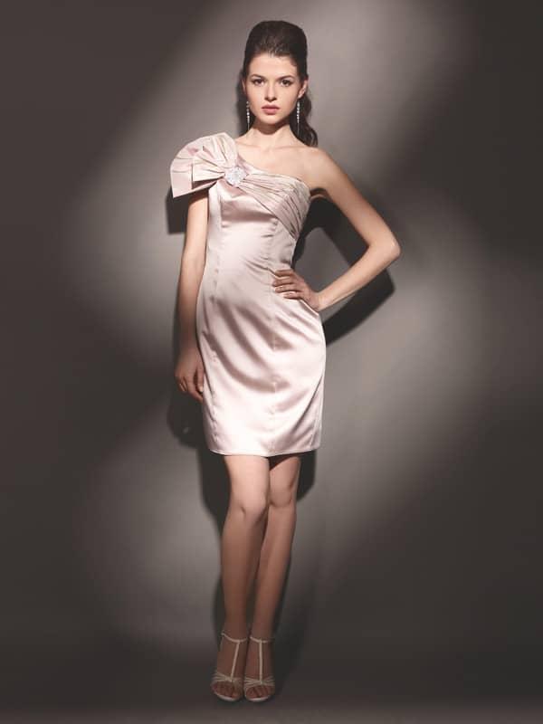 Короткое вечернее платье розового цвета из атласной ткани, украшенное крупным бантом.