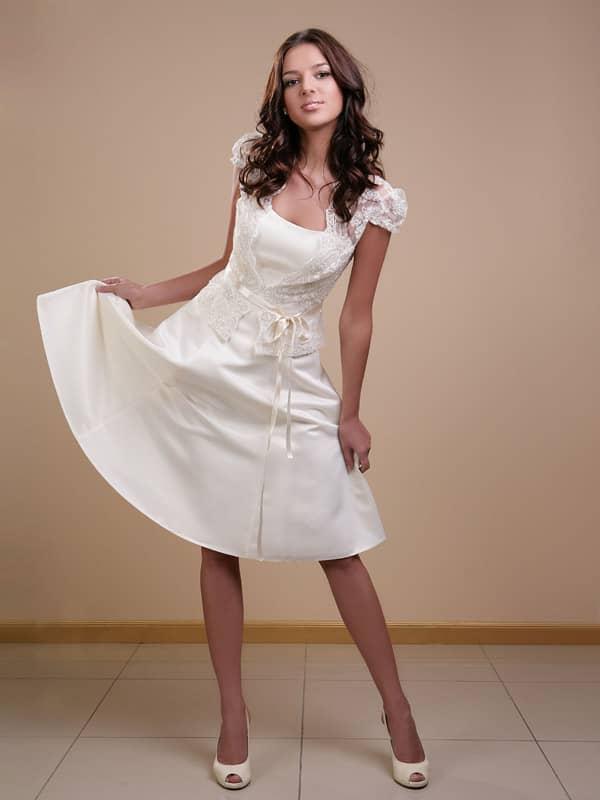Элегантное атласное короткое свадебное платье прилегающего силуэта с плавной линией декольте и расклешённой юбкой-шестиклинкой.